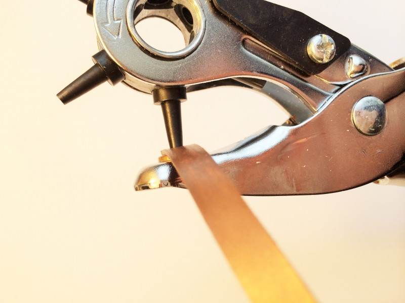 leather hole punch on end of headband